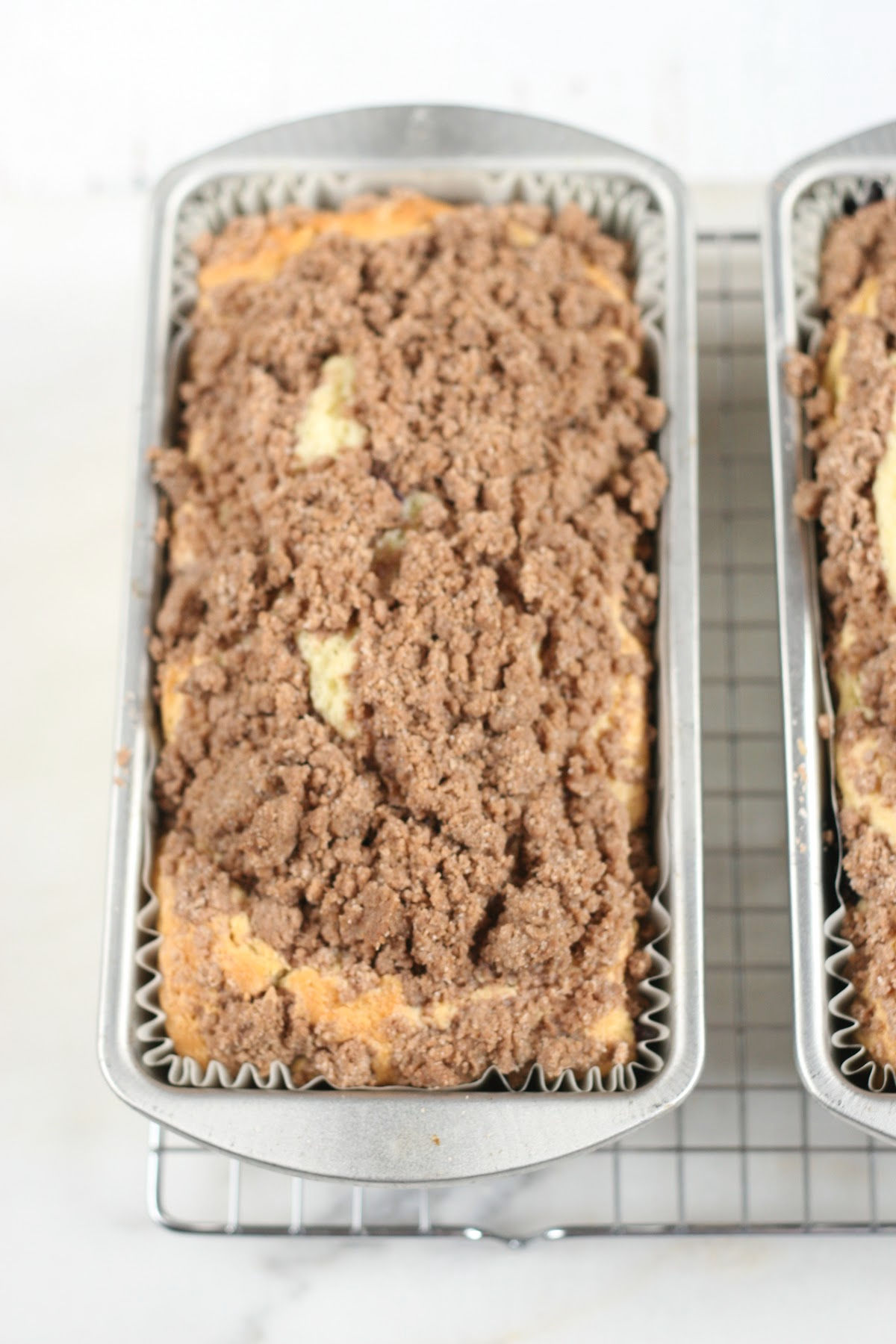 Coffee cake in loaf pans with crumb topping on metal baking rack.