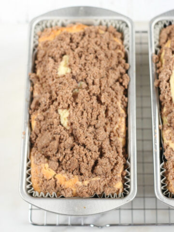 Coffee cake with crumb topping in metal loaf pans on metal baking rack.