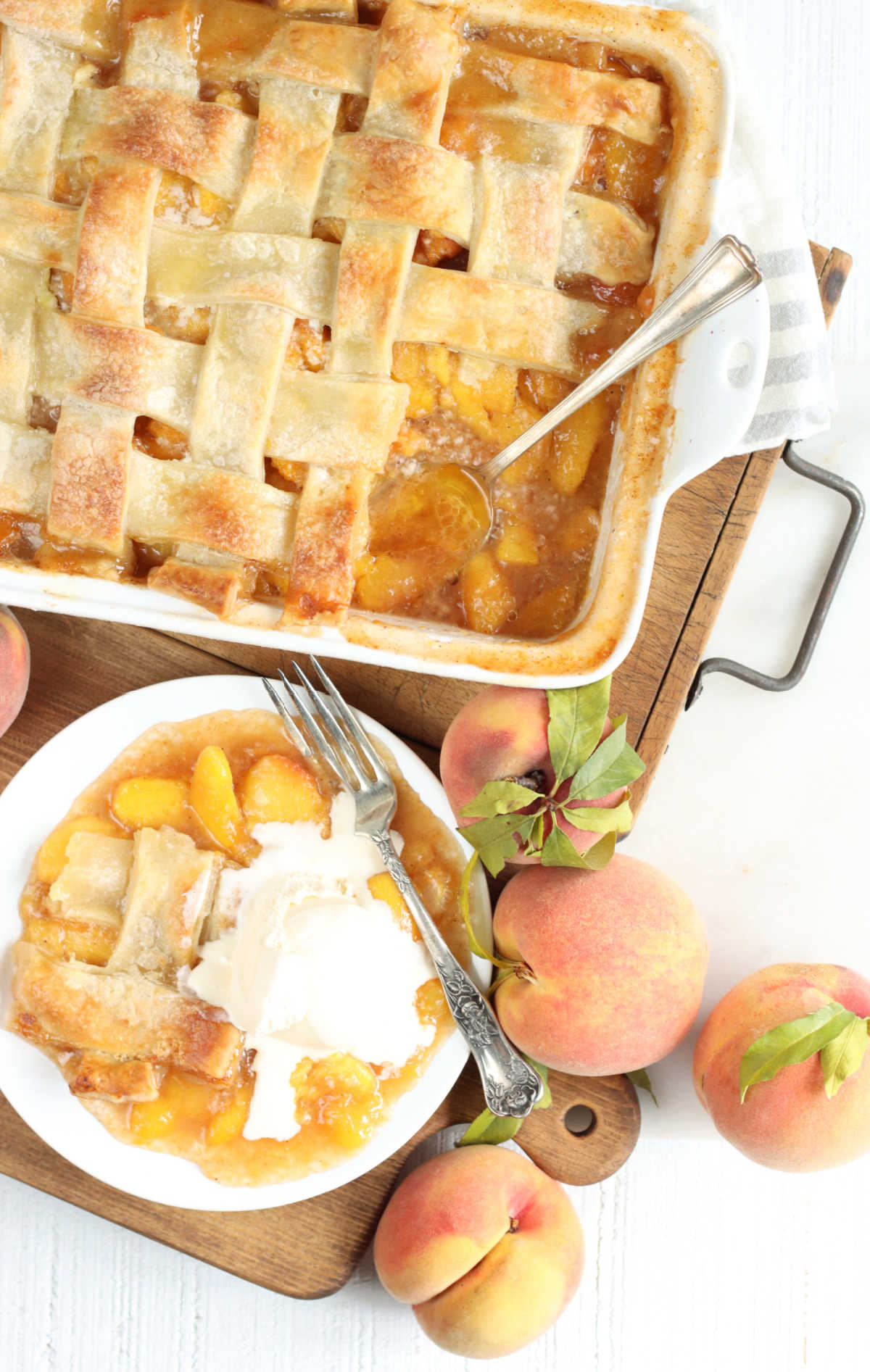 Peach cobbler with pie crust in white baking dish, piece on small white plate and fork, peaches around.