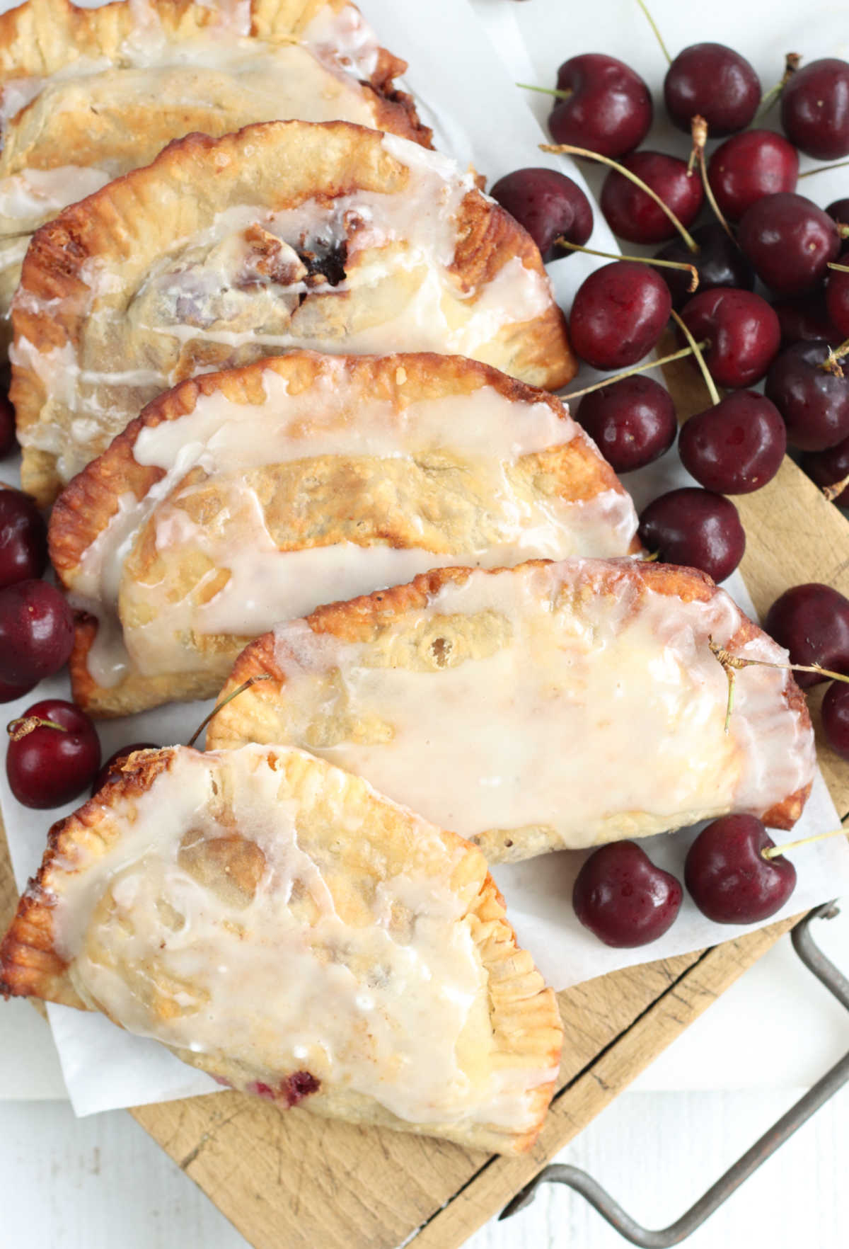 Fried hand pies on wooden cutting board with fresh cherries around.