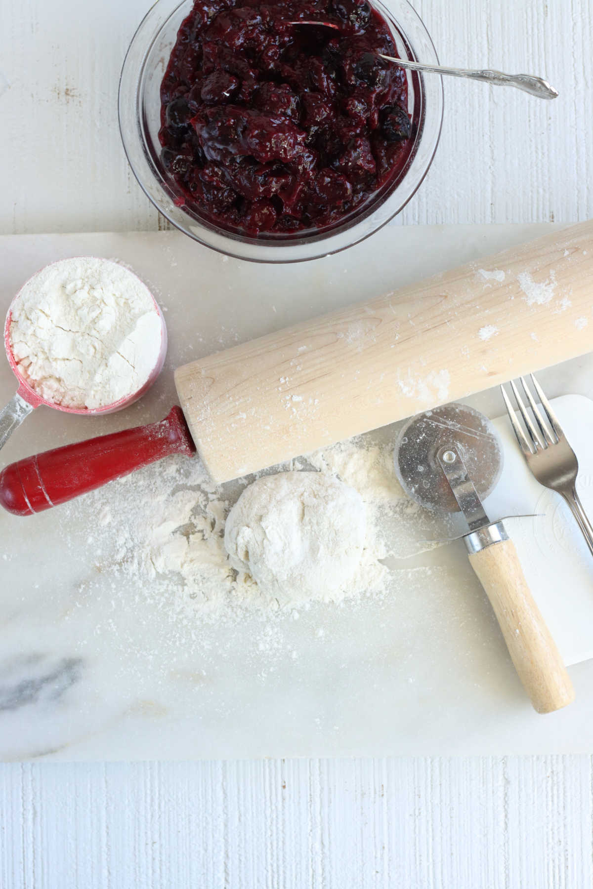 Ingredients for hand pies on white marble, cherry pie filling, pie crust and tools.