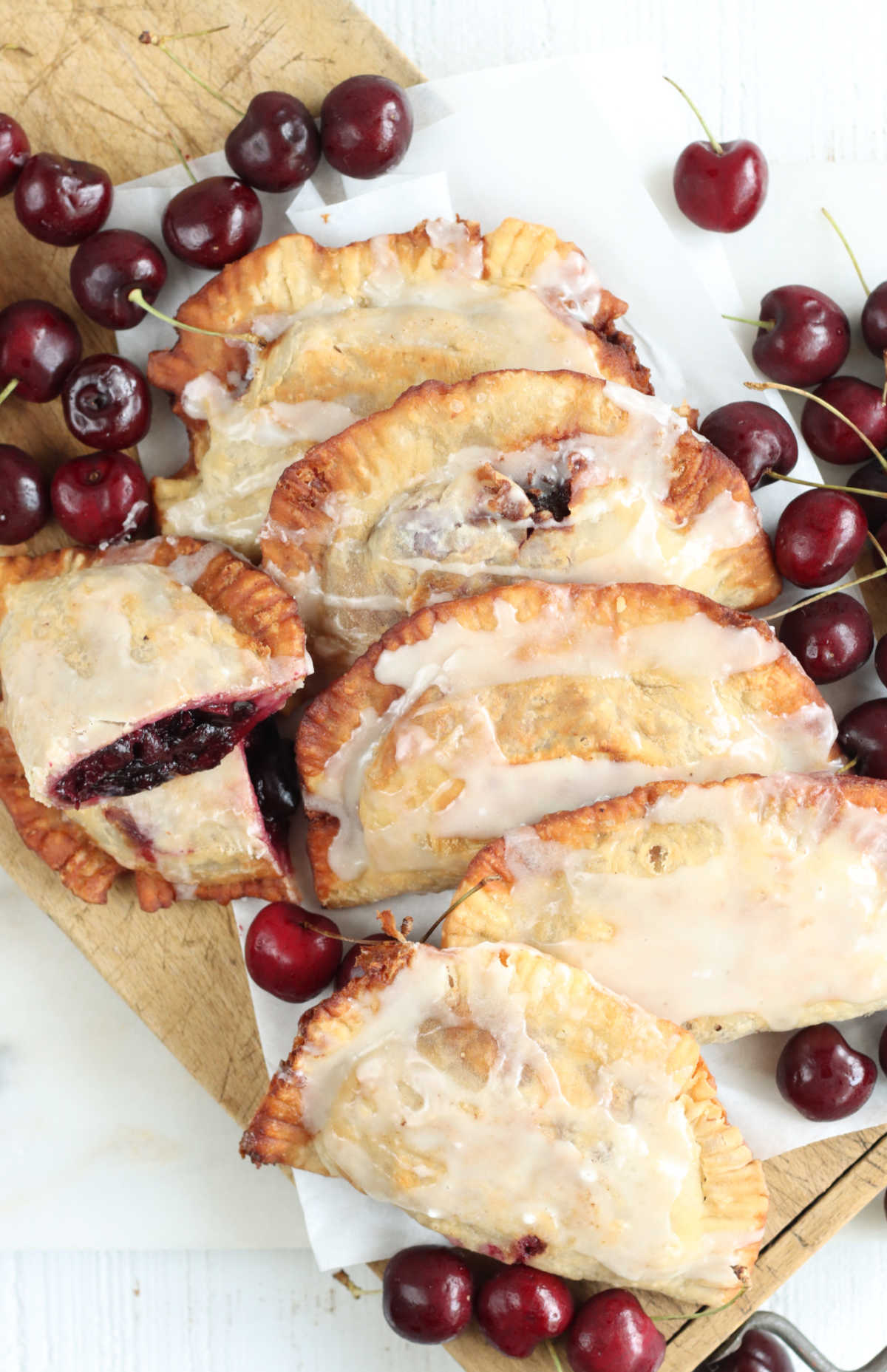 Cherry pies leaning on each other on wooden cutting board, fresh cherries around.