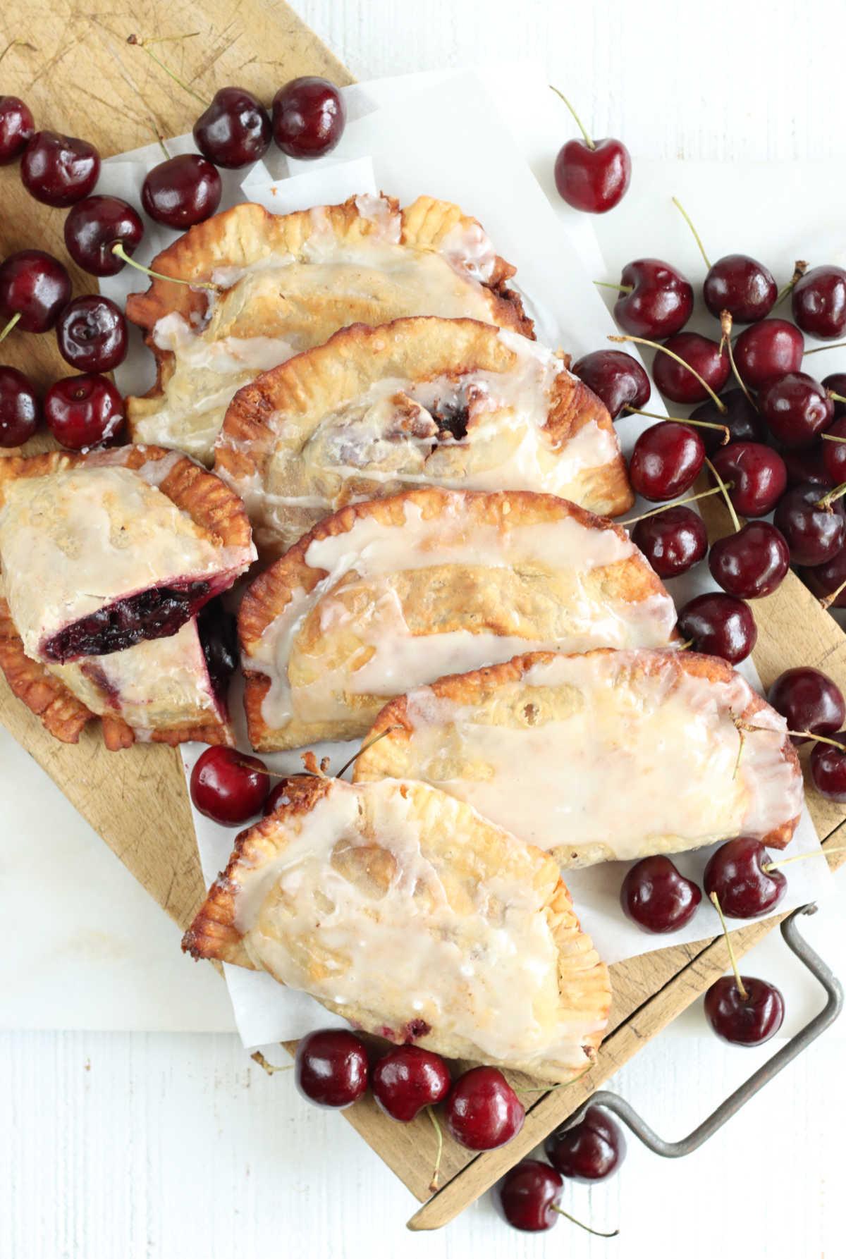 Cherry hand pies on wooden cutting board, fresh cherries around them.