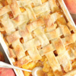 Cobbler with peaches and pie crust in white rectangle baking dish.