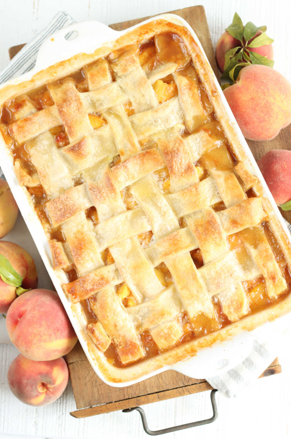 Cobbler with peaches and lattice pie crust in white rectangle baking dish on wooden cutting board, fresh peaches around.