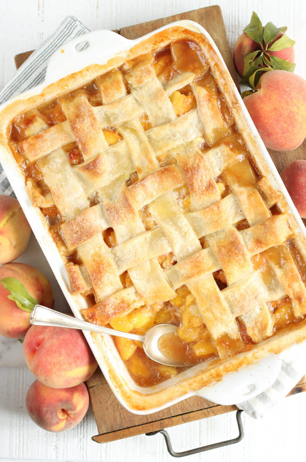 Peach cobbler with pie crust lattice weaved in white rectangle baking dish on wooden cutting board.