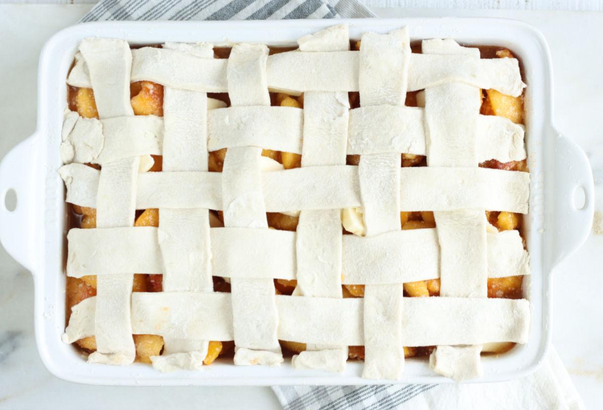 Lattice pie crust on peach cobbler in white baking dish on white marble.
