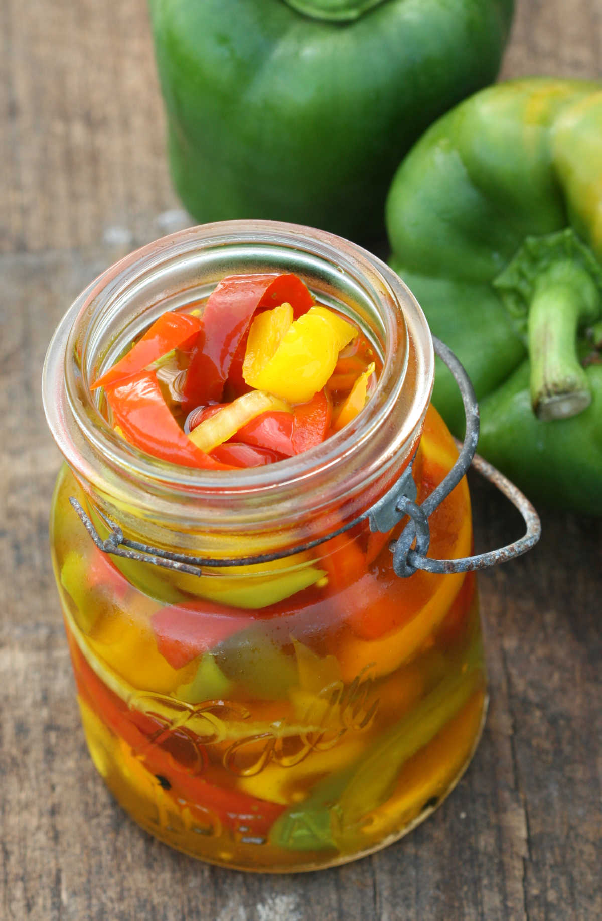 pickled sweet peppers in vintage Mason jars outside on reclaimed wood boards.