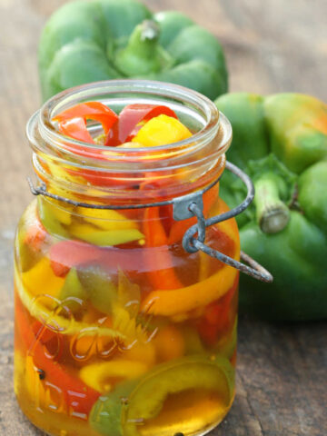 Vintage Mason jars filled with multi color pickled sweet peppers.