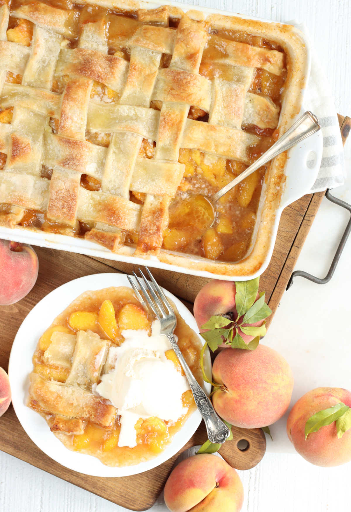 Peach cobbler in white baking dish, white plate with piece of cobbler and fork, fresh peaches around.