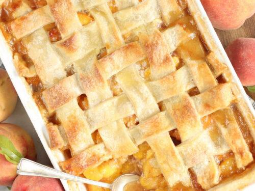 Cobbler with lattice pie crust in white rectangle baking dish, fresh peaches around.