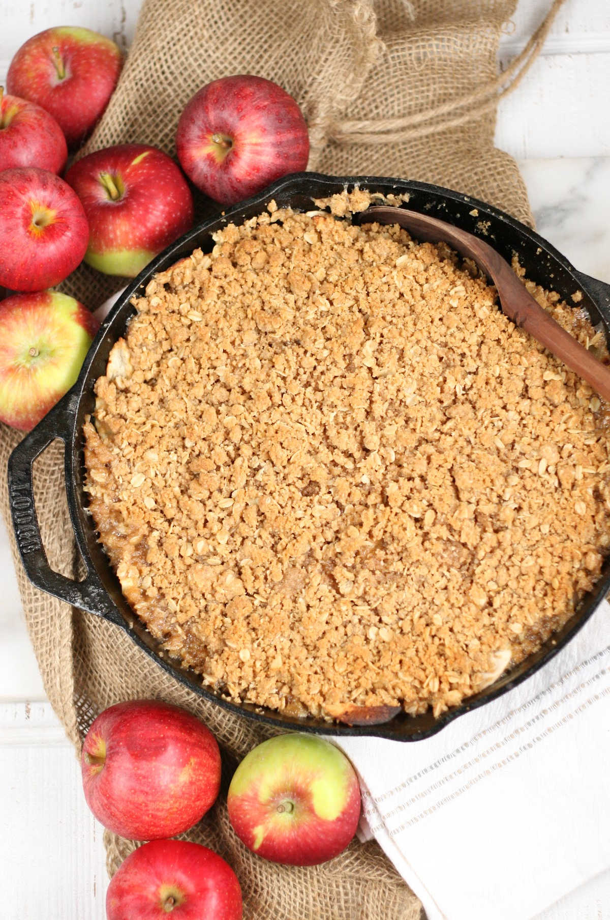 Apple crisp with oatmeal topping in dual handle cast iron skillet, loose apples around.