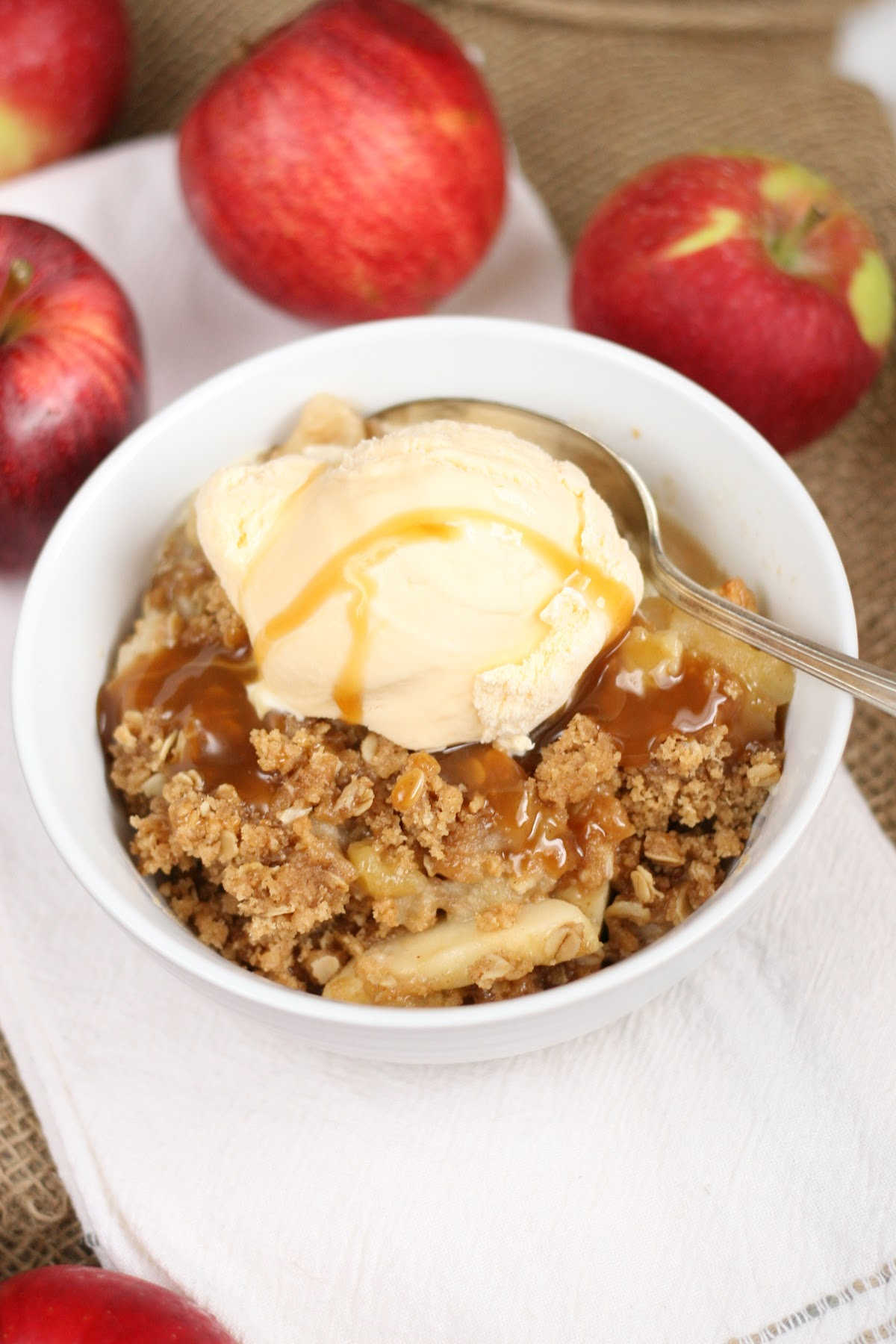 Apple crisp with caramel sauce in small white bowl with spoon.