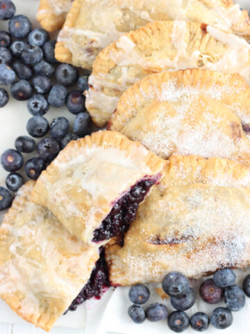 Blueberry hand pies on white marble, one cut in half, fresh blueberries around.