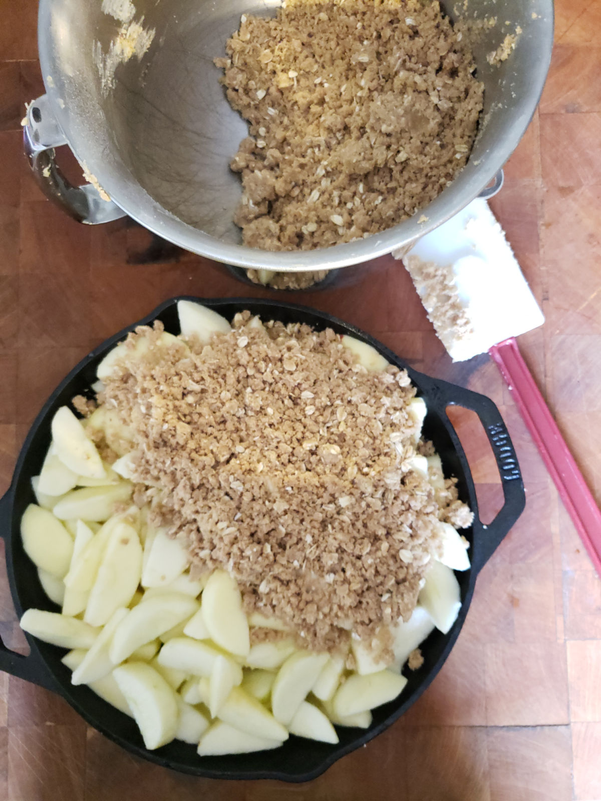 Apples in dual handle cast iron skillet putting crumb topping on, on butcher block.