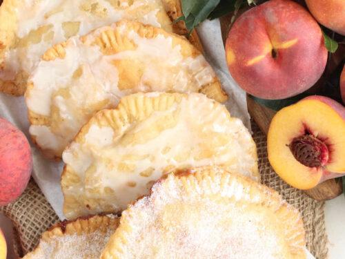 Peach hand pies on burlap, fresh peaches and halves around.