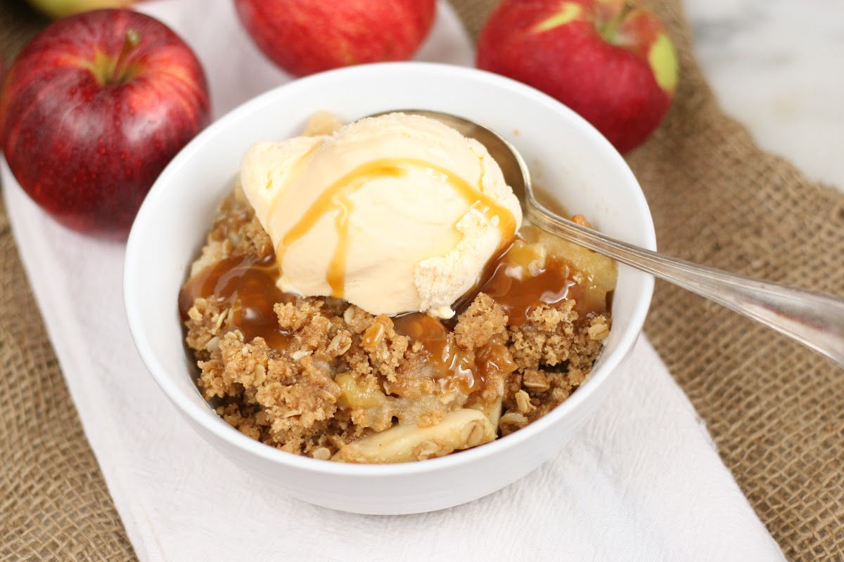 Apple crisp with scoop of vanilla ice cream, caramel sauce and spoon in small white bowl.