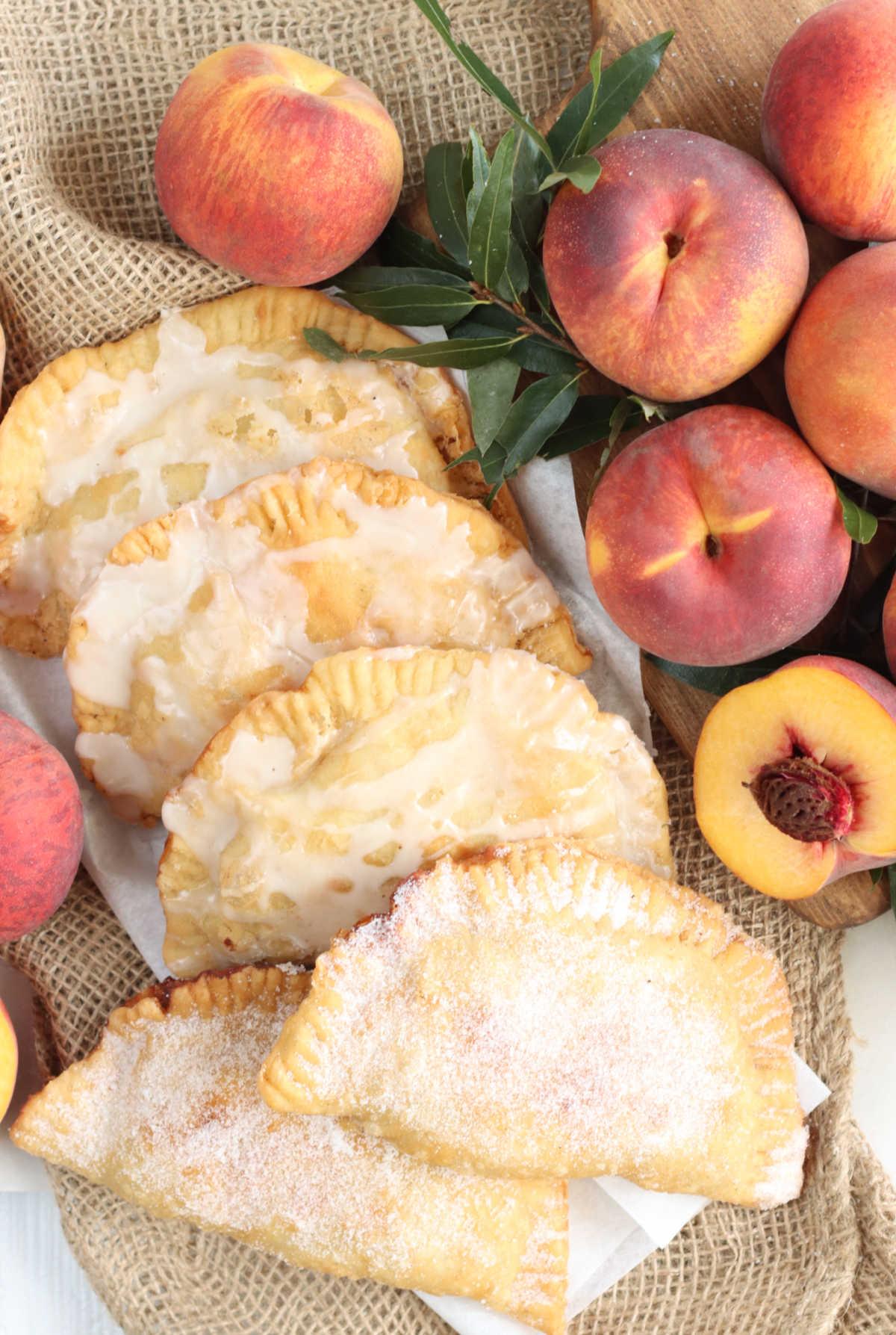 Fried peach hand pies on burlap, fresh peaches around.