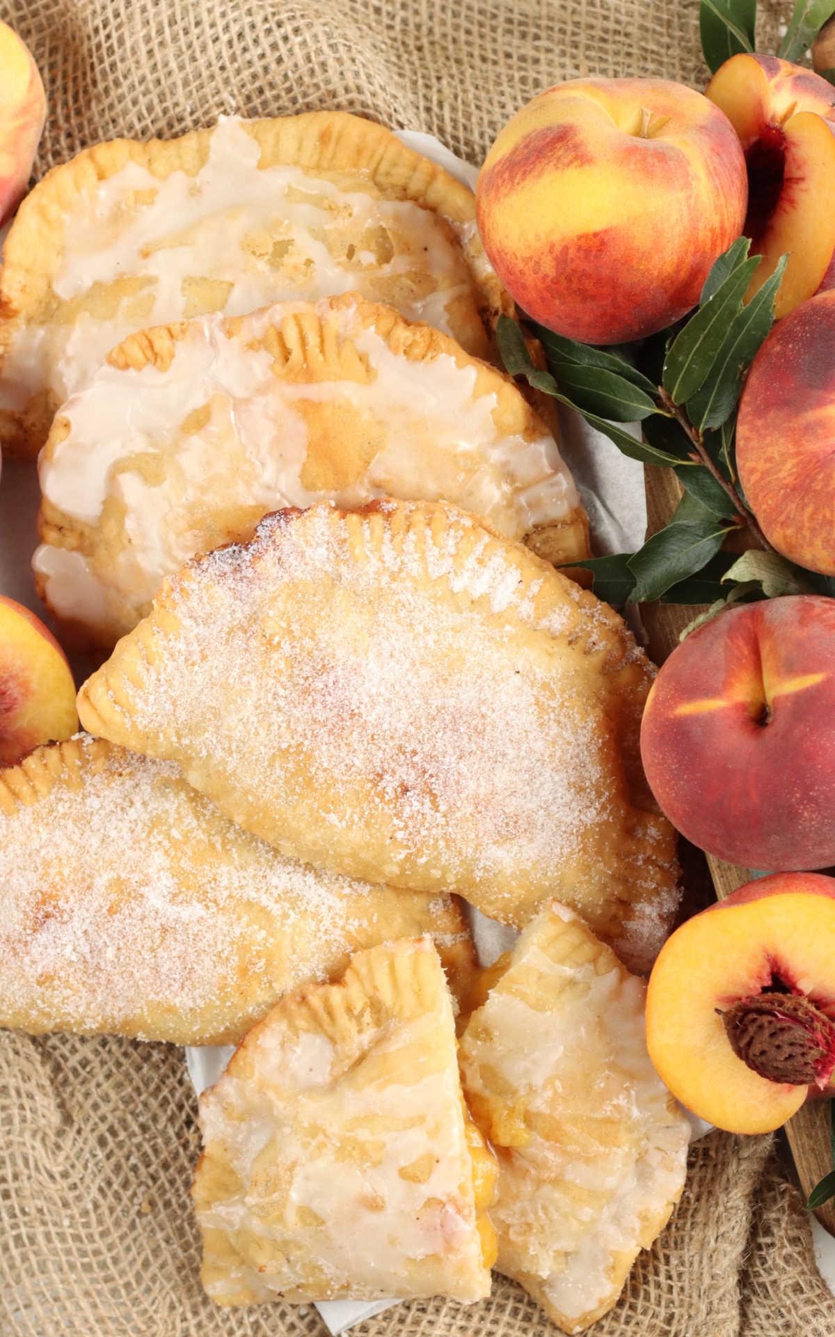 Peach hand pies on burlap, one cut in half, fresh peach halves.