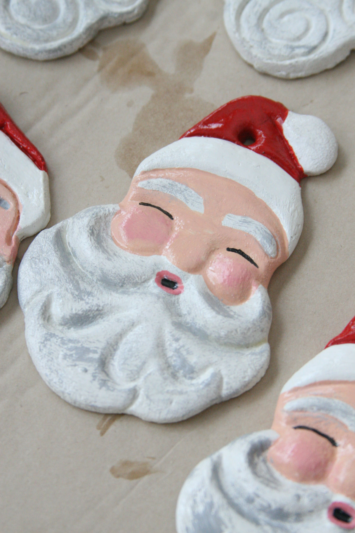 Hand painted Santa face ornaments on brown Kraft paper drying.