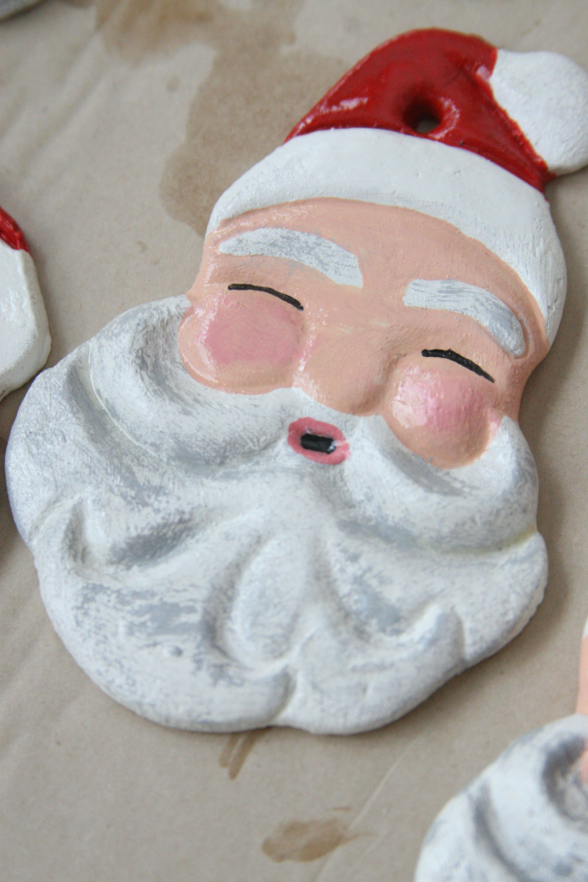 Santa salt dough ornaments with paint drying on brown Kraft paper.