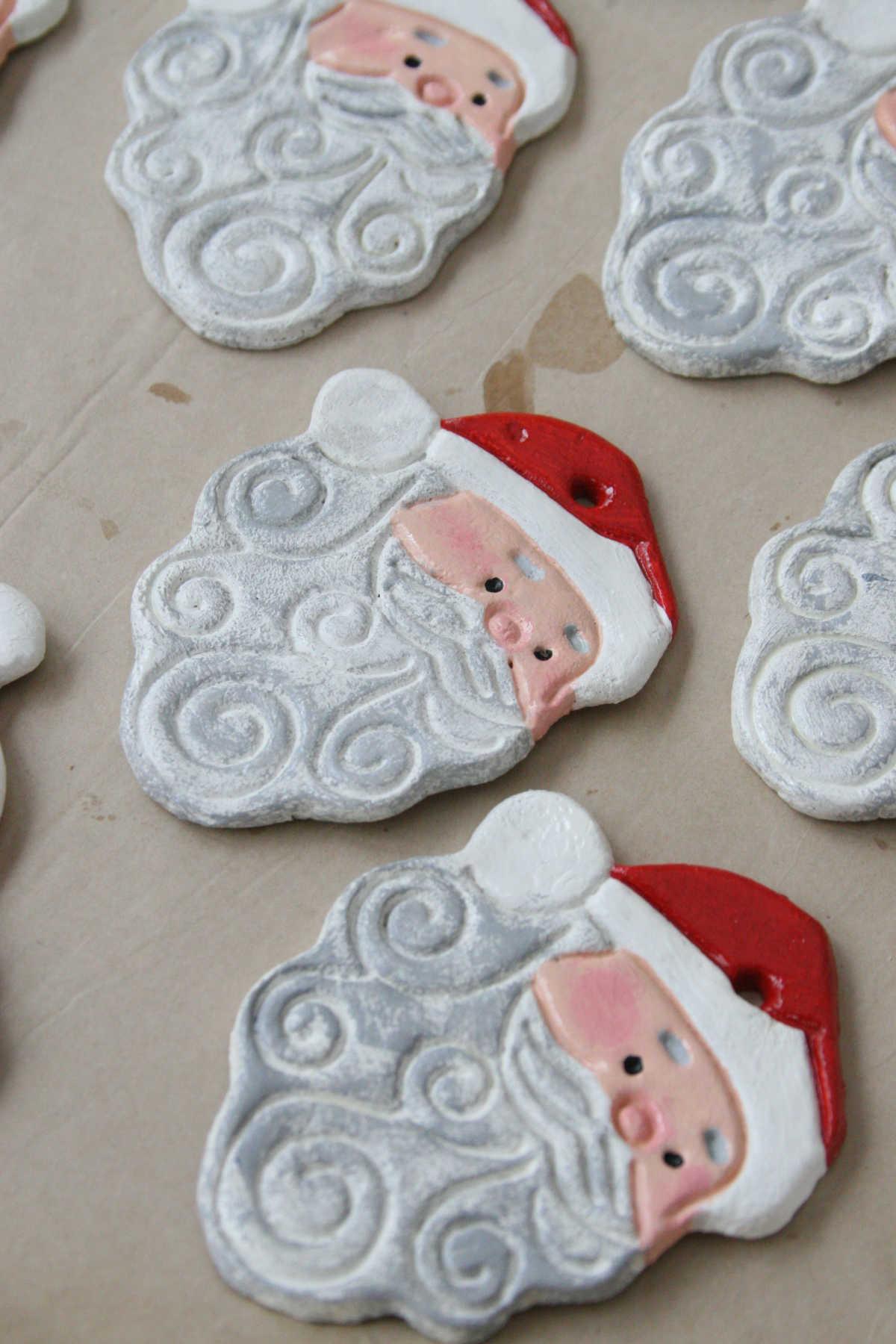 Salt dough ornaments of Santa faces drying on brown Kraft paper.