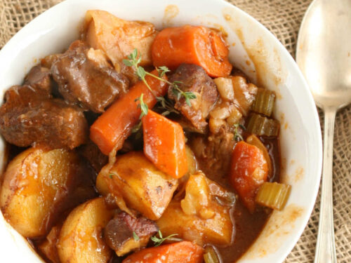 Beef stew with carrots, potatoes, celery in small white bowl, spoon on right.