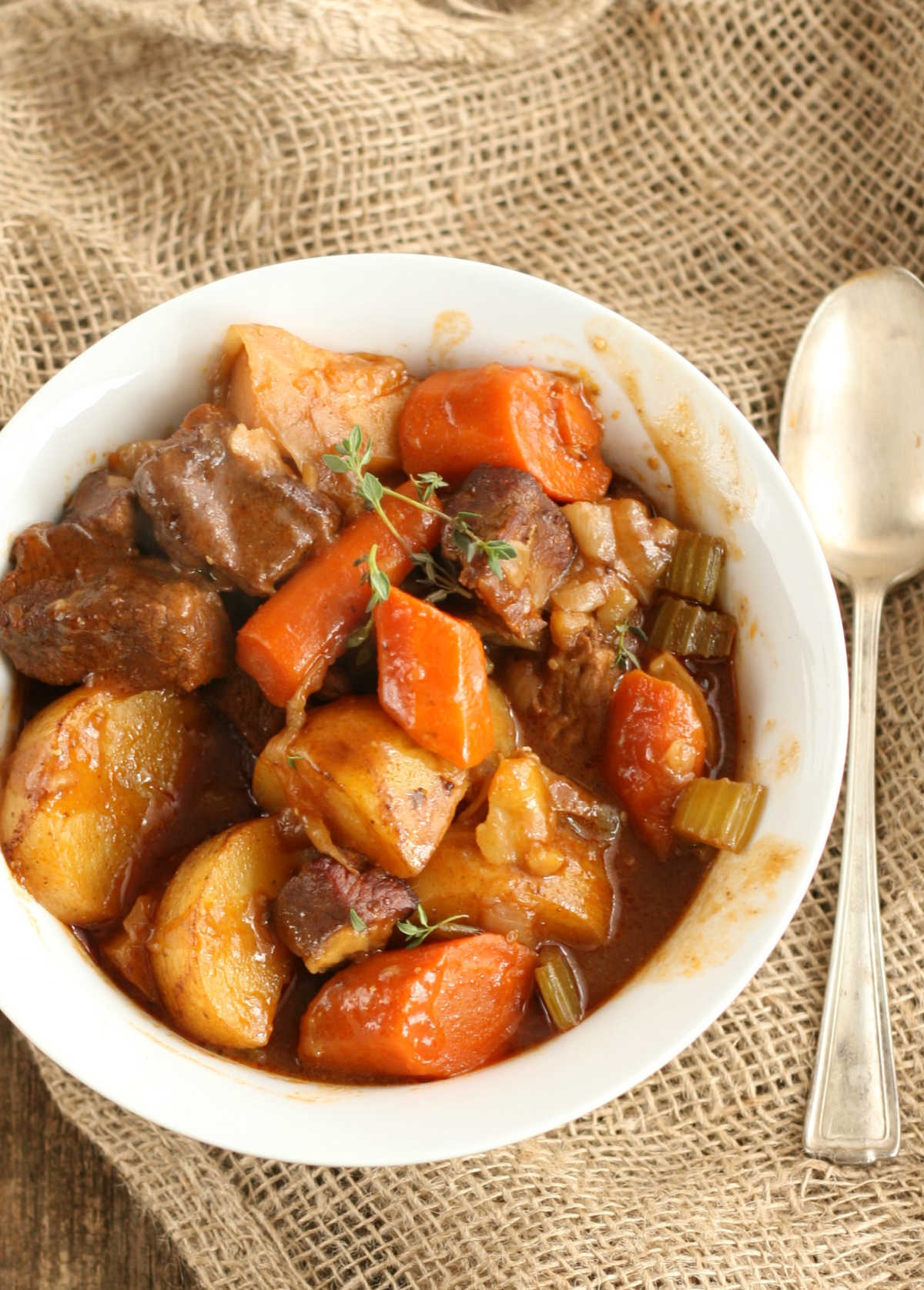 Brisket stew with carrots, stew beef, potatoes, celery, fresh thyme in small white bowl on burlap.