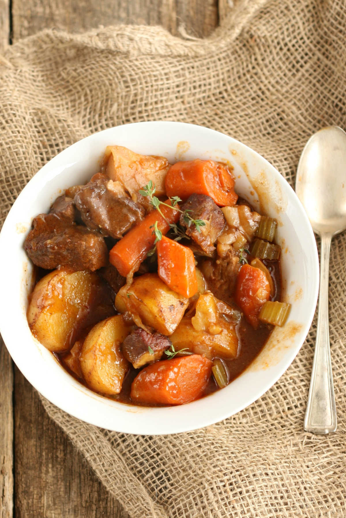 Beef stew with carrots, potatoes, celery, in small white bowl, spoon on right.