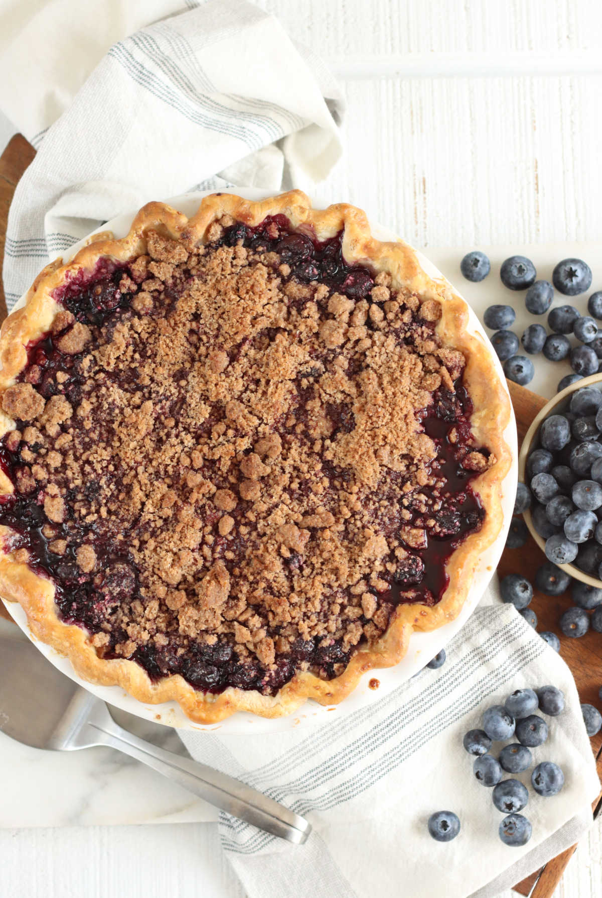 Blueberry pie with crumb topping on cutting board, kitchen towel, metal pie server, fresh blueberries.