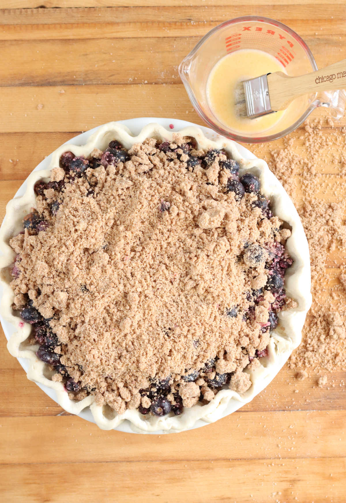 Blueberry pie with crumb topping on wooden cutting board, egg wash and pastry brush in glass measuring cup.