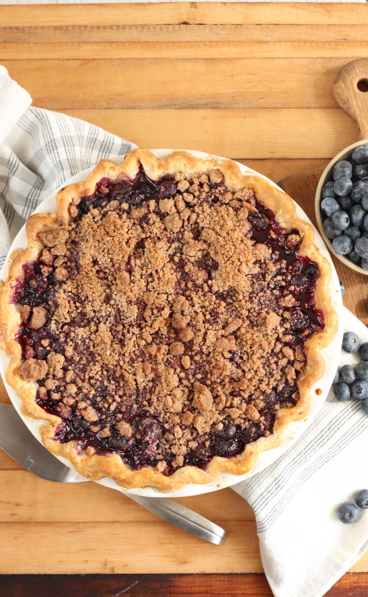 Blueberry pie crumble topping on butcher block, metal pie server and fresh blueberries.