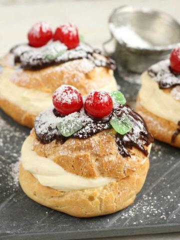 Cream puffs pastry cream and chocolate ganache, maraschino cherries and powdered sugar.