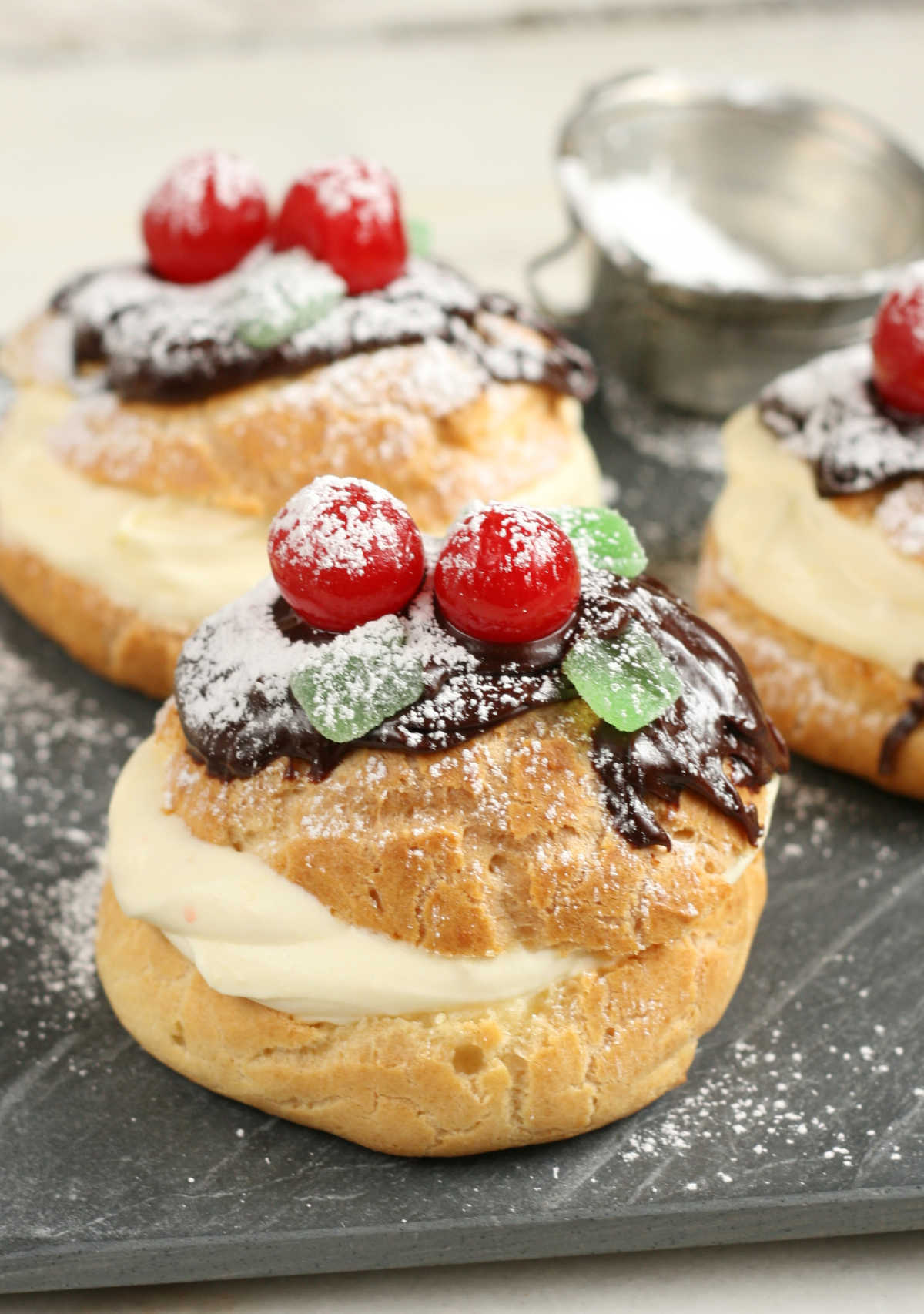 Cream puffs with pastry cream, chocolate ganache, maraschino cherries, green leaf candies dusted with powdered sugar.