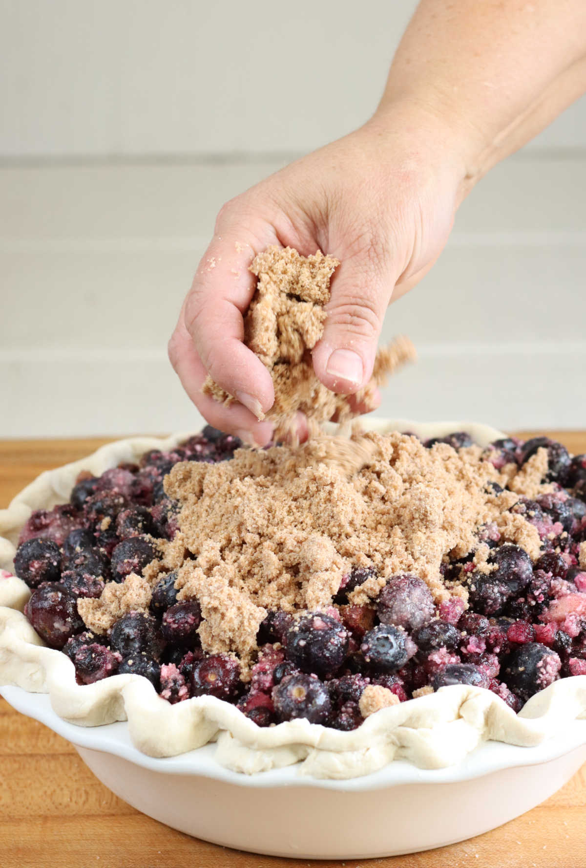 Hand pouring crumb topping on blueberry pie in white pie dish on butcher block.