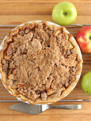 Apple crumb pie in white pie dish on butcher block, apples around.