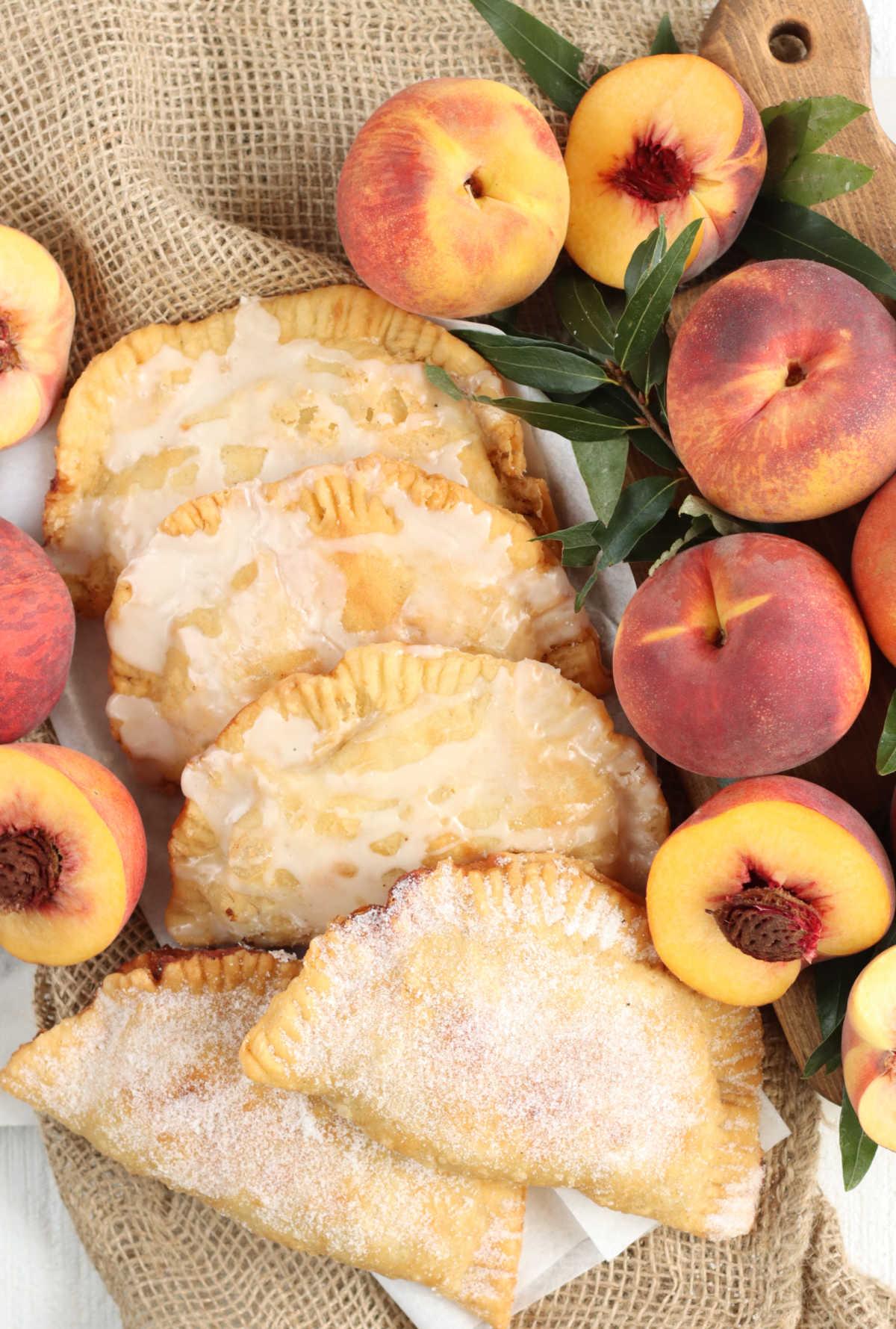 Fried peach pies on burlap, fresh peaches and halves around.