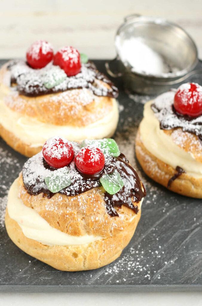 Cream puffs with pastry cream, chocolate ganache, maraschino cherries, green mint candies, powdered sugar.